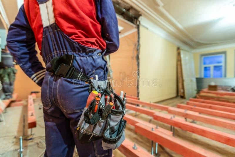 O trabalhador da construção com baf do workwear e da ferramenta com as ferramentas na cintura no apartamento é construção do inde fotos de stock royalty free