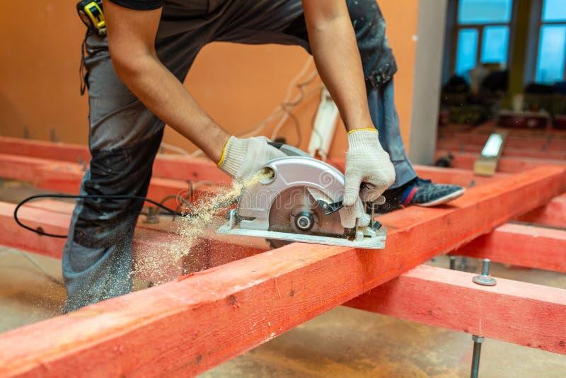 O trabalhador da construção com circular elétrica viu que bloco de madeira das serras e muita poeira da serra no apartamento são  fotos de stock royalty free