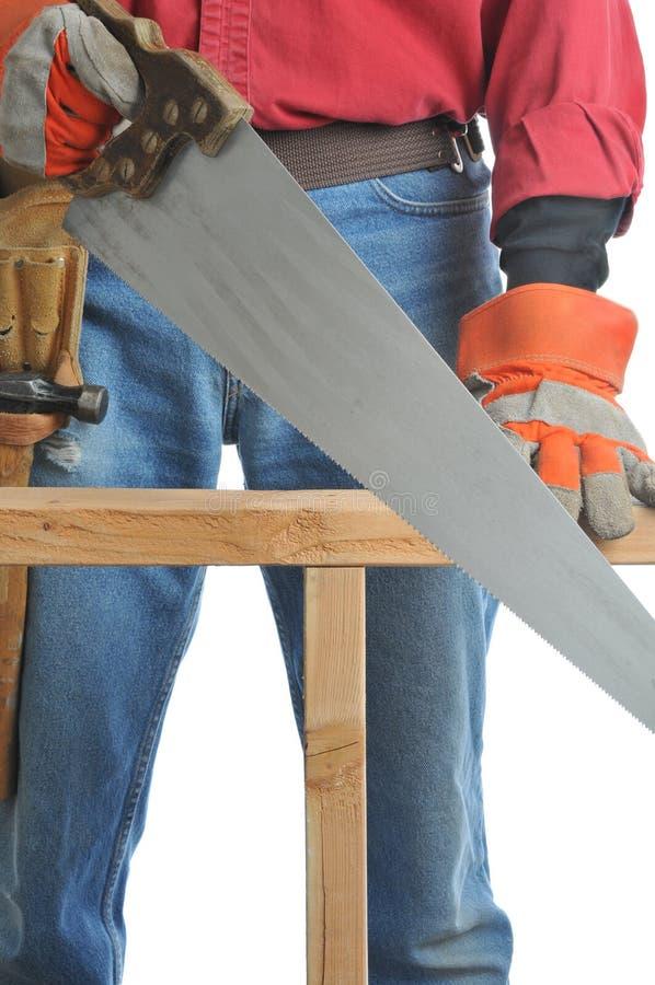 O trabalhador da construção com mão viu fotos de stock