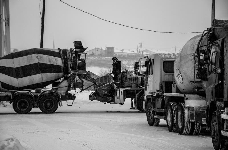 O trabalhador da construção está em um misturador concreto em uma foto preto e branco fotografia de stock royalty free