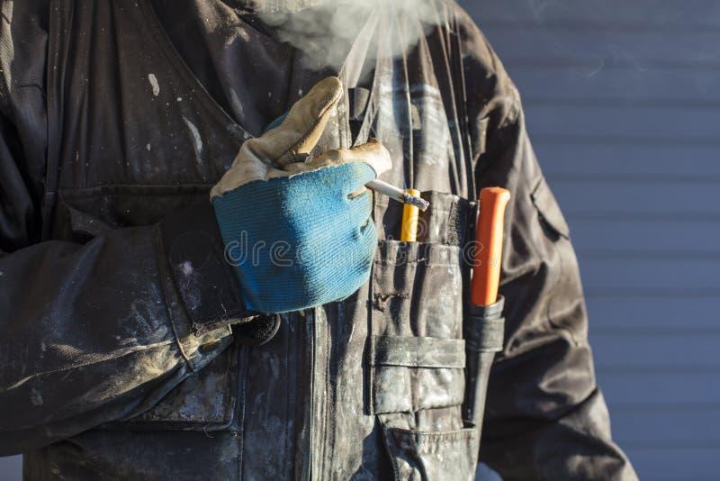 O trabalhador da construção fuma um cigarro em Finlandia fotografia de stock royalty free