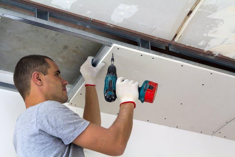 O trabalhador da construção monta um teto suspendido com o drywall foto de stock royalty free