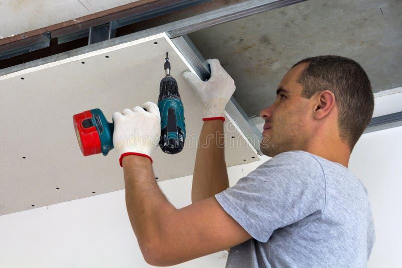 O trabalhador da construção monta um teto suspendido com o drywall imagem de stock