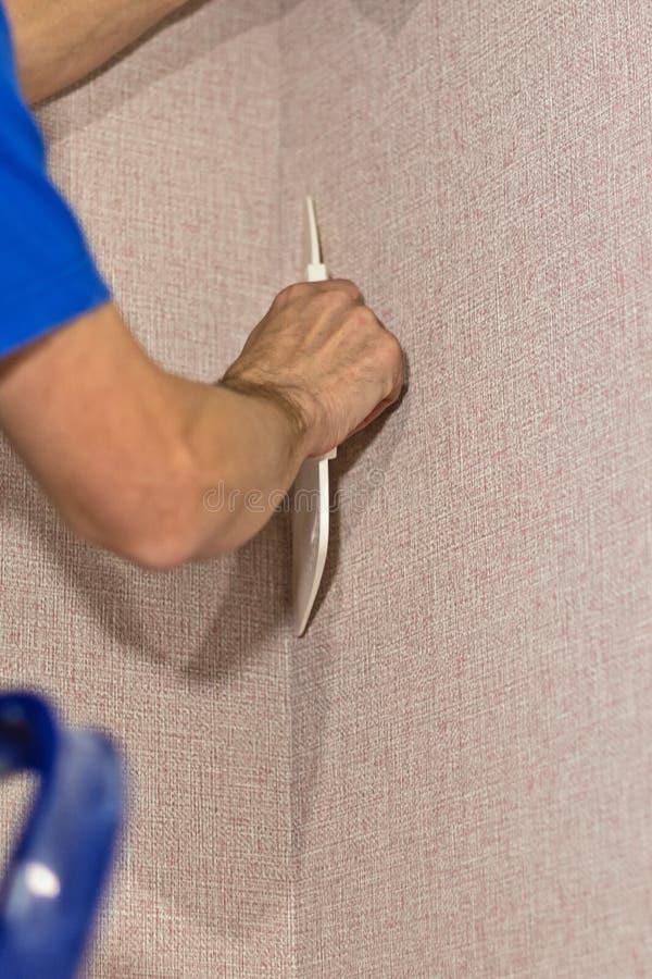 O trabalhador da construção usa uma espátula de pintura para alinhar o papel de parede imagem de stock