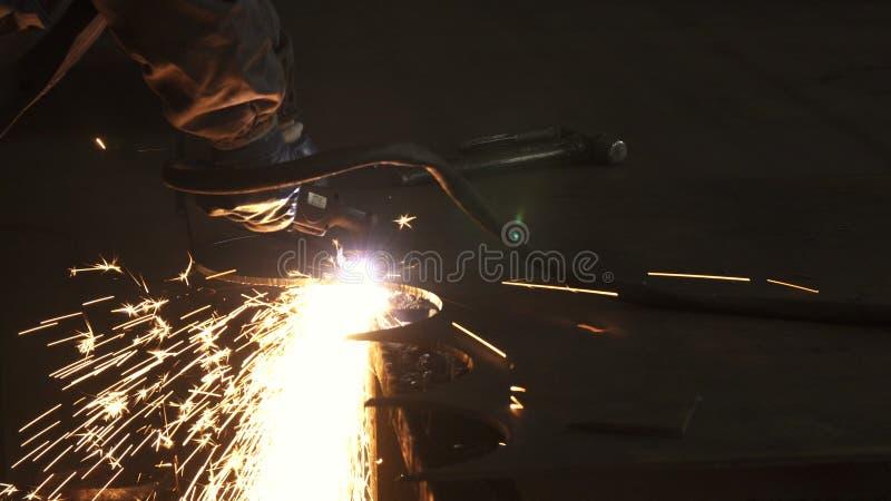 O trabalhador da indústria no corte uniforme protetor metal manualmente foto de stock