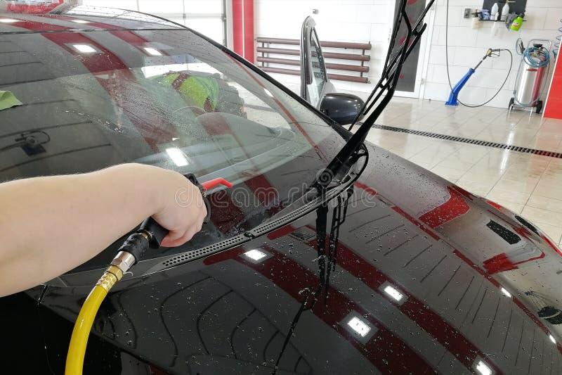 o trabalhador da lavagem de carros funde a parte dianteira do carro com ar comprimido imagem de stock