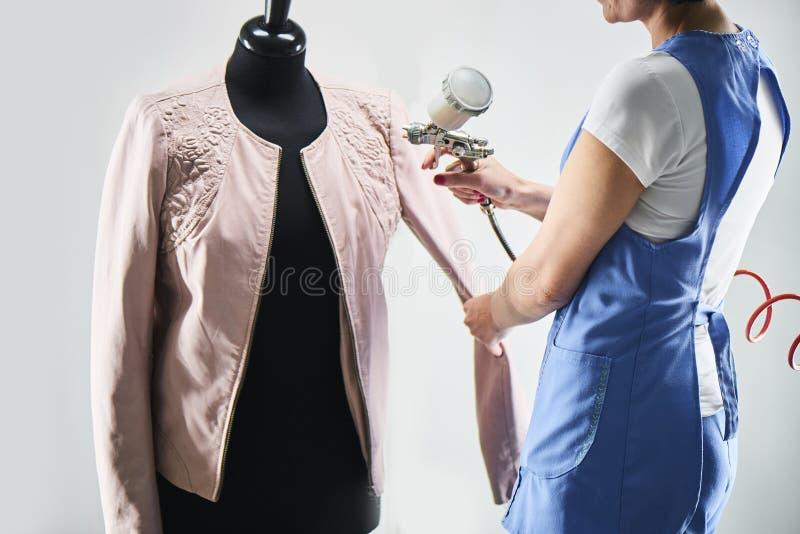 O trabalhador da lavanderia da menina executa casacos de cabedal da pintura em um manequim imagens de stock royalty free