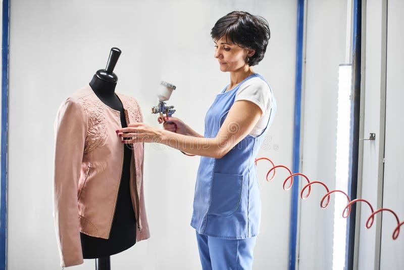O trabalhador da lavanderia da menina executa casacos de cabedal da pintura em um manequim foto de stock royalty free