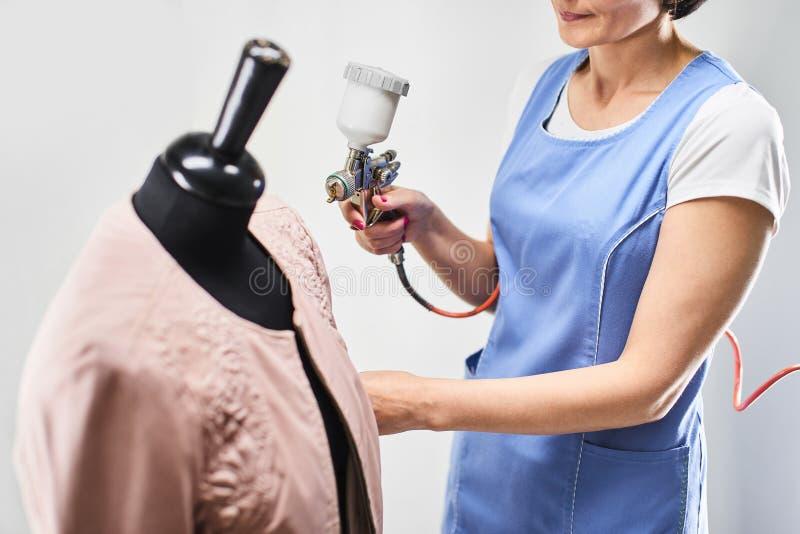 O trabalhador da lavanderia da menina executa casacos de cabedal da pintura em um manequim fotografia de stock royalty free