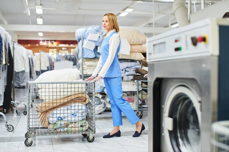 O trabalhador da lavanderia da menina rola um carro com material limpo imagem de stock royalty free