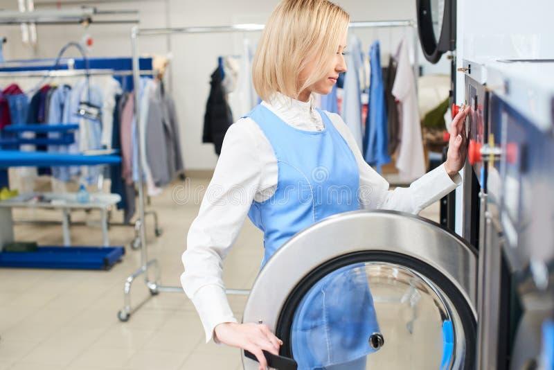 O trabalhador da lavanderia da menina seleciona um programa da lavagem imagem de stock