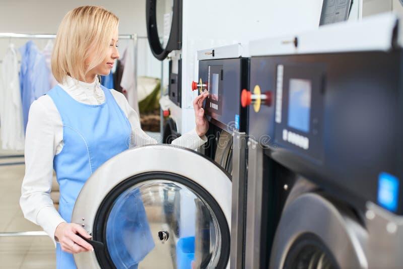 O trabalhador da lavanderia da menina seleciona um programa da lavagem imagem de stock royalty free