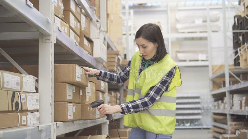 O trabalhador da loja no armazém que usa um varredor do código de barras conduz a contabilidade foto de stock