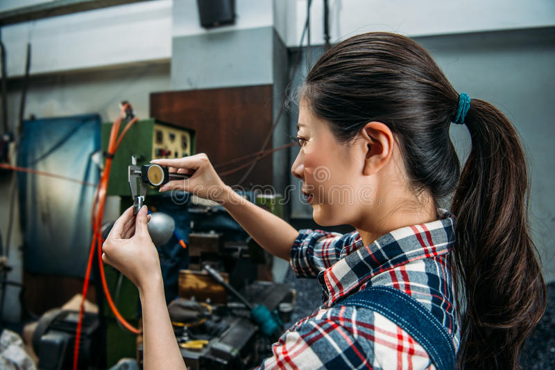O trabalhador da máquina de trituração verifica o aço da fabricação foto de stock
