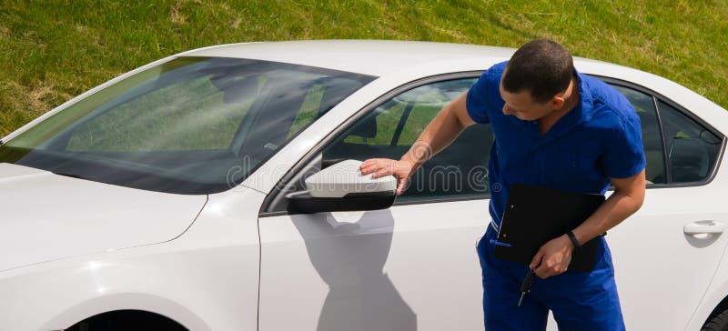 O trabalhador da manutenção em um terno azul guarda um papel de escrita em sua mão e inspeciona o carro imagens de stock