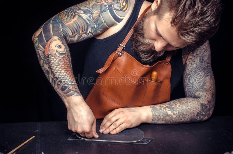 O trabalhador de couro forma o produto de couro novo em sua loja do curtidor fotografia de stock
