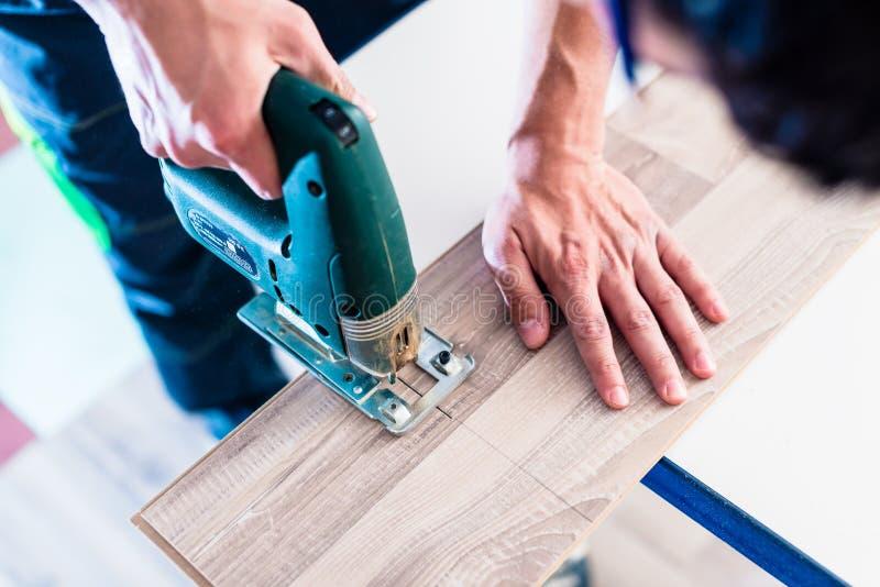 O trabalhador de DIY que corta o painel de madeira com gabarito viu fotografia de stock