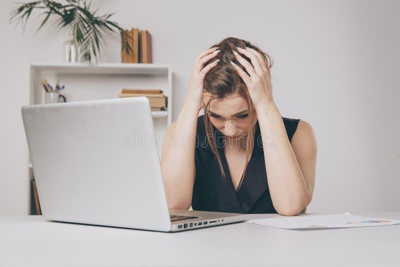 O trabalhador de escritório fêmea novo cansado e tem uma dor de cabeça conceito da enxaqueca foto de stock royalty free
