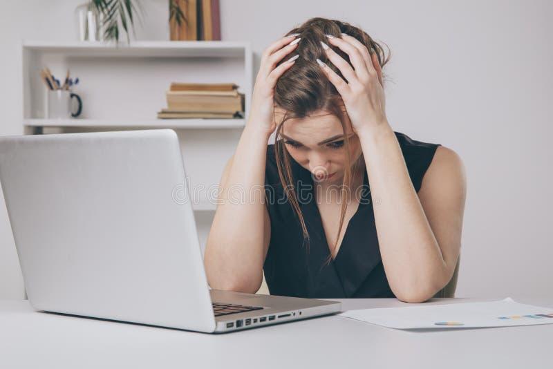 O trabalhador de escritório fêmea novo cansado e tem uma dor de cabeça conceito da enxaqueca imagem de stock royalty free
