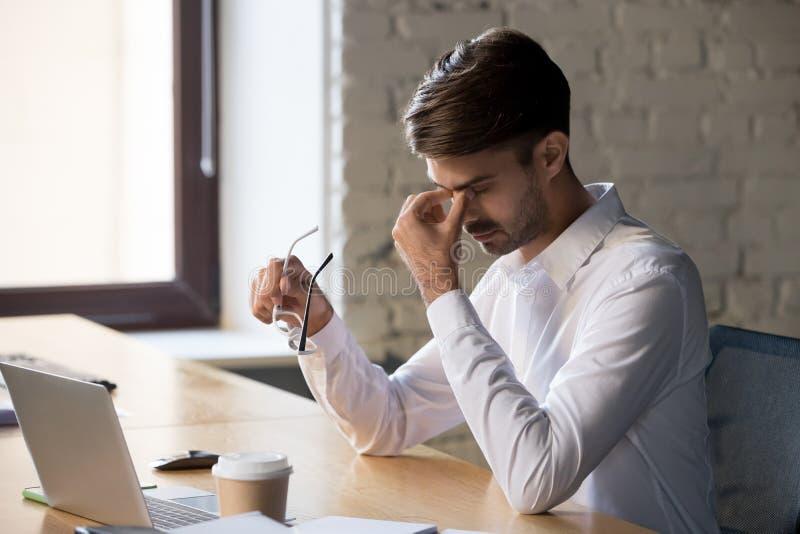 O trabalhador de escritório milenar que decola monóculos sofre da tensão de olhos imagem de stock