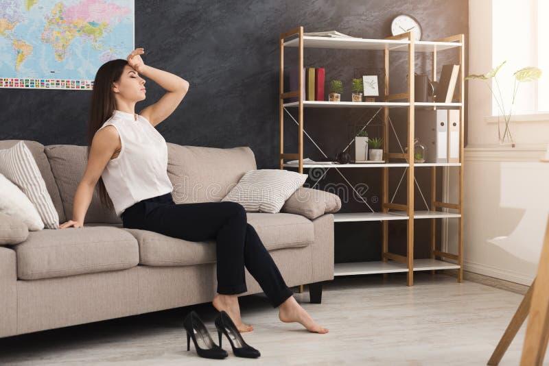 O trabalhador de escritório terminou o trabalho e o assento no sofá imagens de stock royalty free