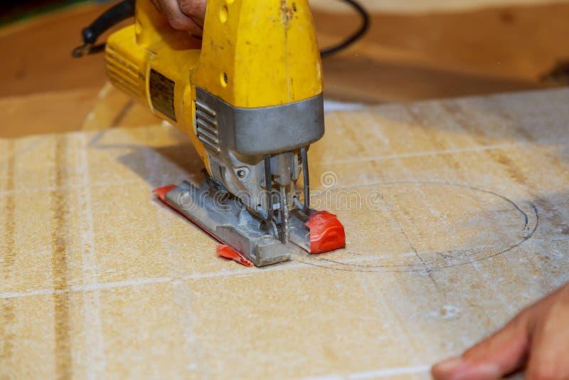o trabalhador de madeira que corta o painel de madeira com gabarito viu fora, opinião do close-up o homem foto de stock