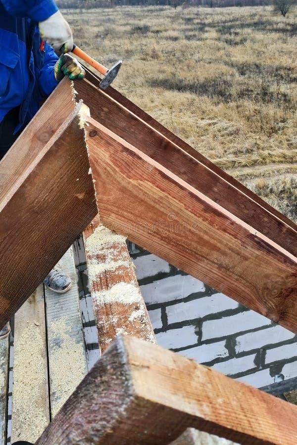 o trabalhador dispara nas vigas no quadro do telhado imagens de stock