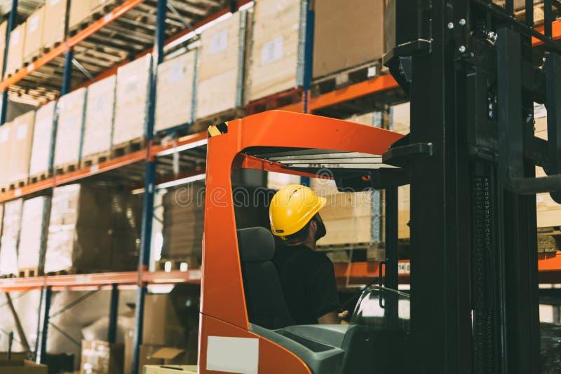 O trabalhador do armazém que faz a logística trabalha com carregador da empilhadeira fotografia de stock
