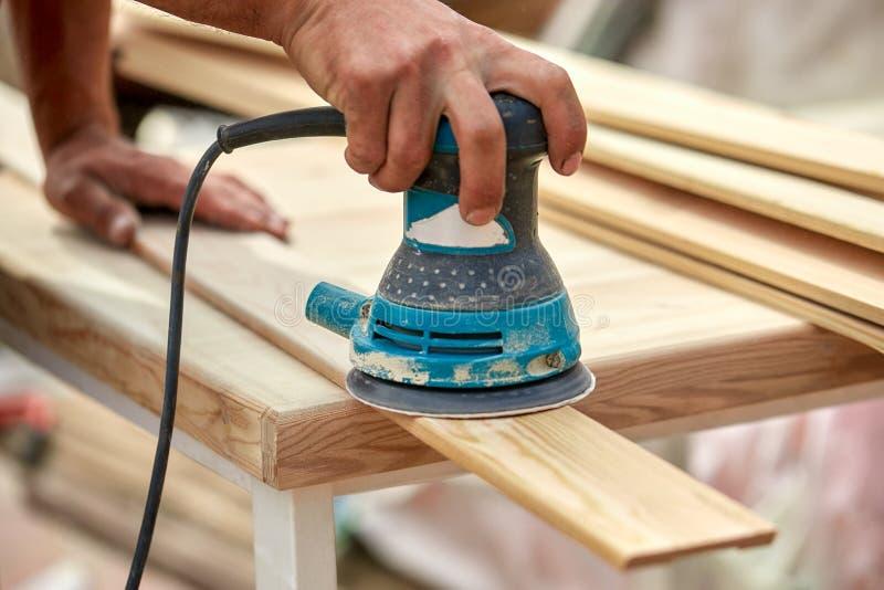 O trabalhador do moedor lustra uma placa de madeira Máquina excêntrica orbital de lixamento das placas imagem de stock