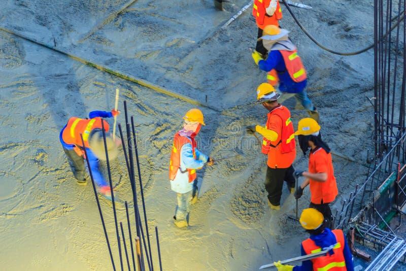 O trabalhador do pedreiro que nivela o concreto com pás de pedreiro, pedreiro entrega o spreadi fotografia de stock royalty free