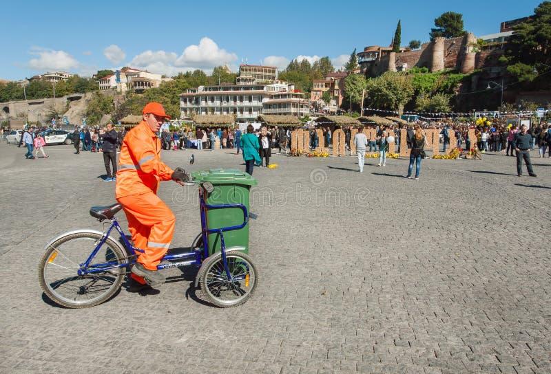 O trabalhador do serviço da cidade no uniforme limpa a rua do lixo em uma bicicleta foto de stock royalty free