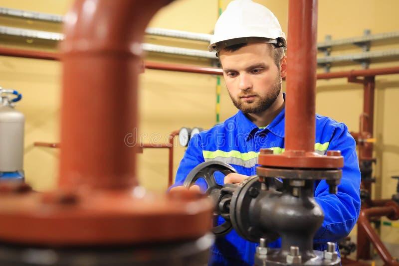 O trabalhador do técnico gerencie a válvula na caldeira de aquecimento industrial fotos de stock royalty free