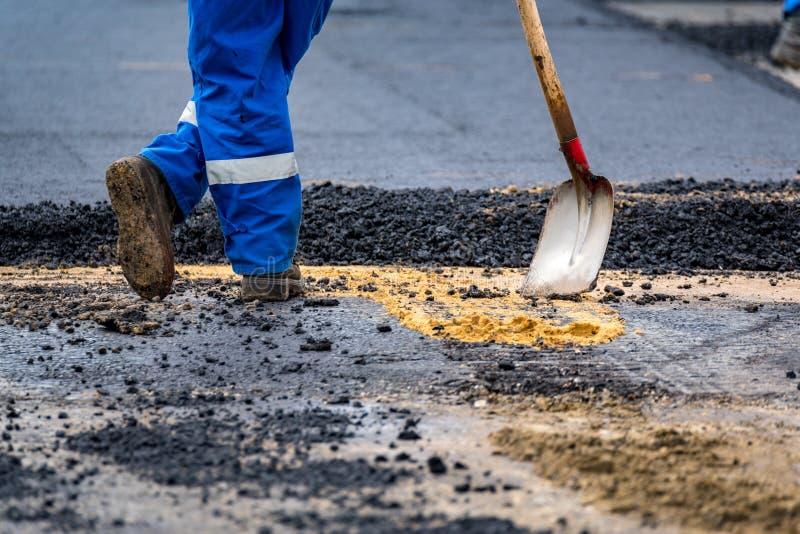 O trabalhador e as máquinas de asfaltagem fotografia de stock