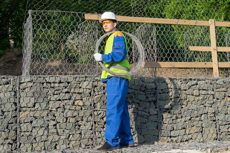 O trabalhador em uma veste amarela e em um capacete branco, leva um rolo do fio em seu ombro fotografia de stock