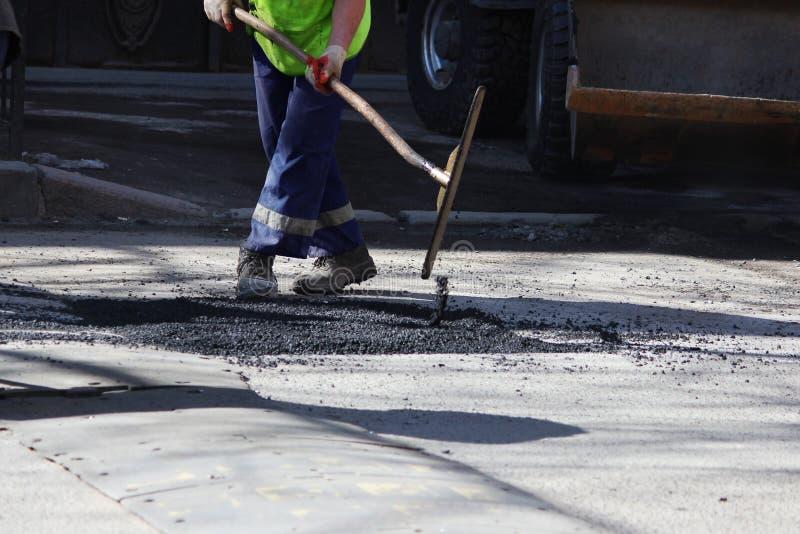 O trabalhador está nivelando a migalha do asfalto no poço com um arrasto-rolo antes de pavimentar com rolo da construção da estra fotos de stock