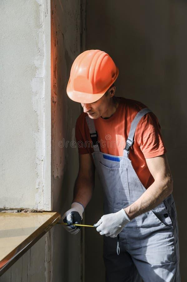 O trabalhador está verificando a exatidão da instalação de um vento imagens de stock
