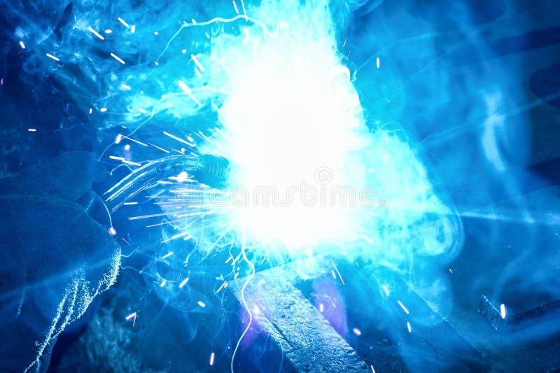 O trabalhador executa o trabalho de solda na planta, na soldadura, no fumo e no fogo fotografia de stock royalty free
