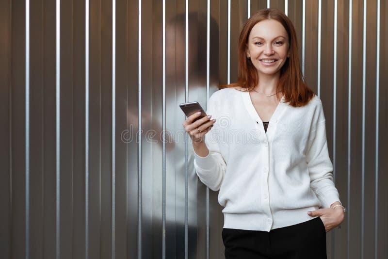 O trabalhador fêmea bonito vestido na roupa incorporada, dinheiro do negócio de transferências através do app depositar em linha  imagem de stock royalty free