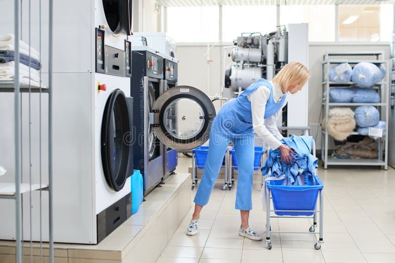 O trabalhador fêmea carrega a roupa da lavanderia na máquina de lavar fotografia de stock