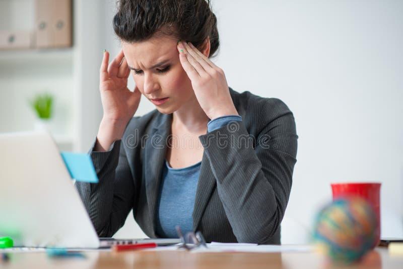 O trabalhador fêmea tem a dor em sua cabeça imagem de stock