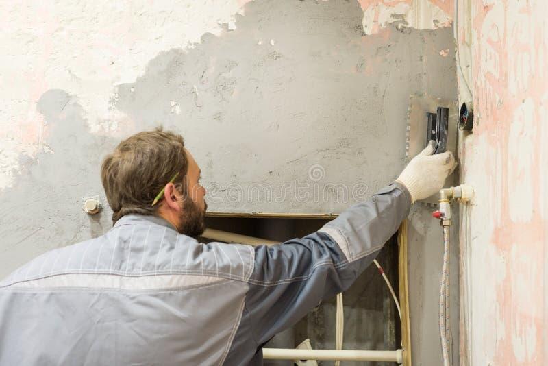 O trabalhador faz o emplastro do muro de cimento foto de stock