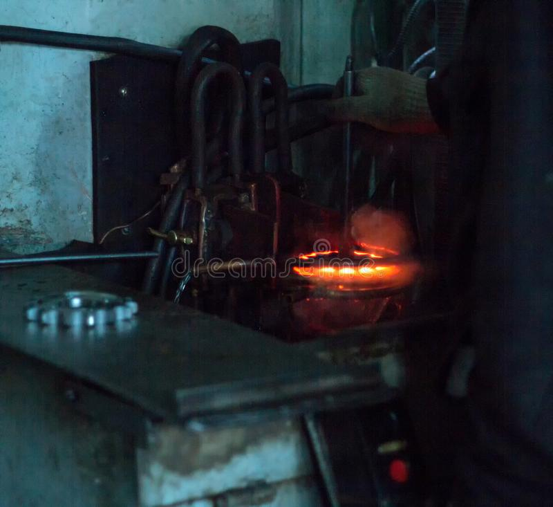 O trabalhador faz o endurecimento do tratamento térmico da engrenagem do metal em uma máquina especial, close-up, endurecimento d imagem de stock