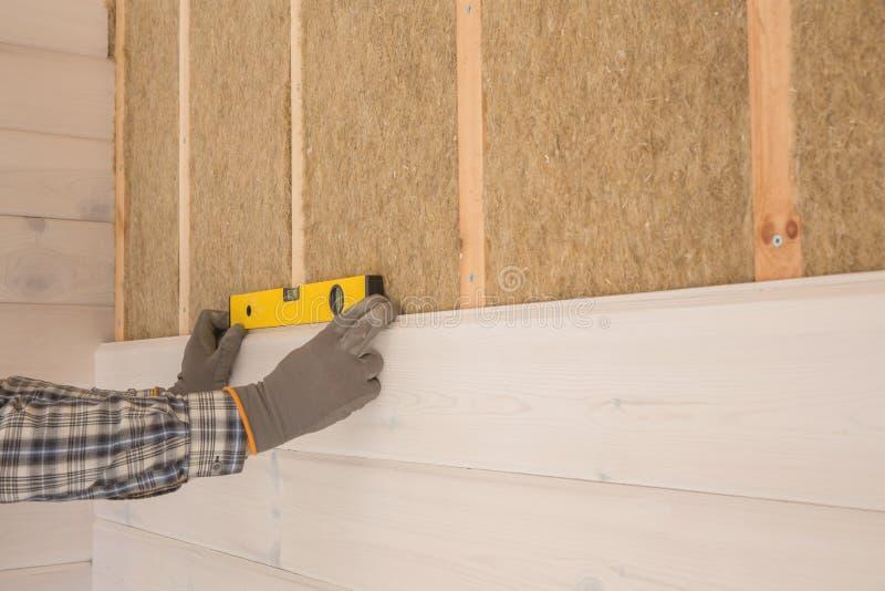O trabalhador faz trabalhos do revestimento das paredes com uma placa de madeira branca, usando a linha nível do laser Calor-isol foto de stock