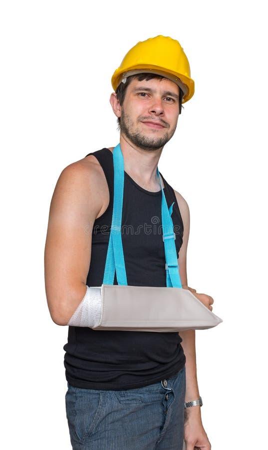 O trabalhador ferido é de sorriso e vestindo o estilingue médico em seu braço Isolado no fundo branco fotos de stock