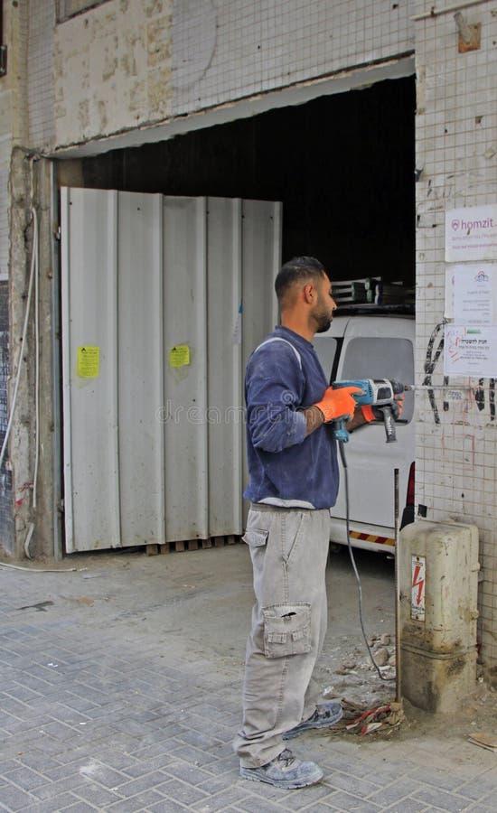 O trabalhador fura um furo na parede fora imagem de stock