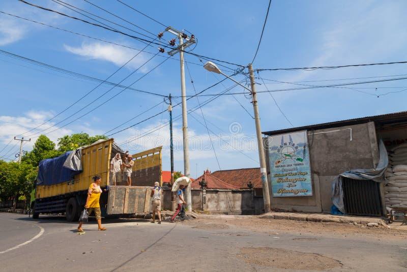 O trabalhador indonésio carrega sacos do arroz de um caminhão imagens de stock