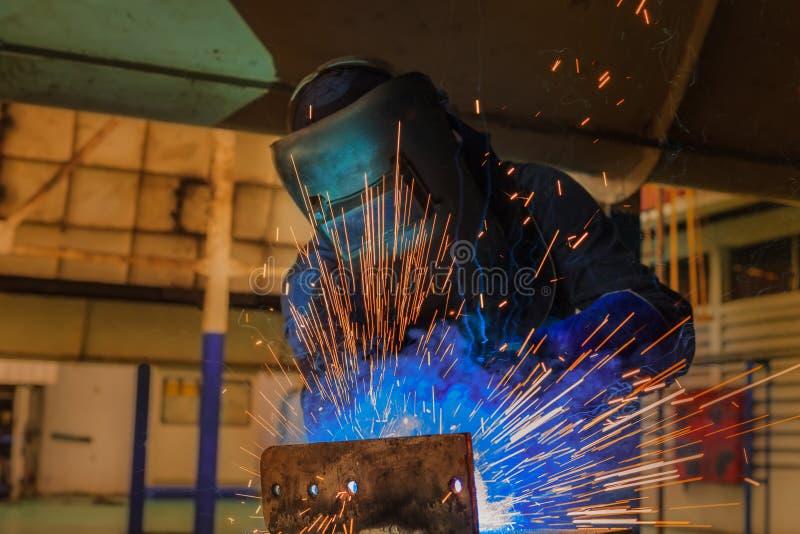O trabalhador industrial é metal de soldadura na fábrica fotografia de stock royalty free