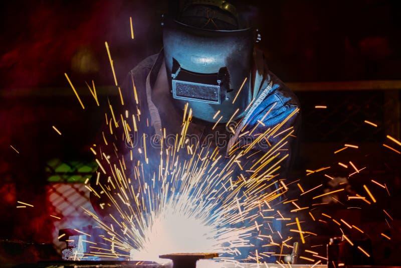 O trabalhador industrial está soldando a peça de metal do reparo na fábrica do carro imagem de stock royalty free