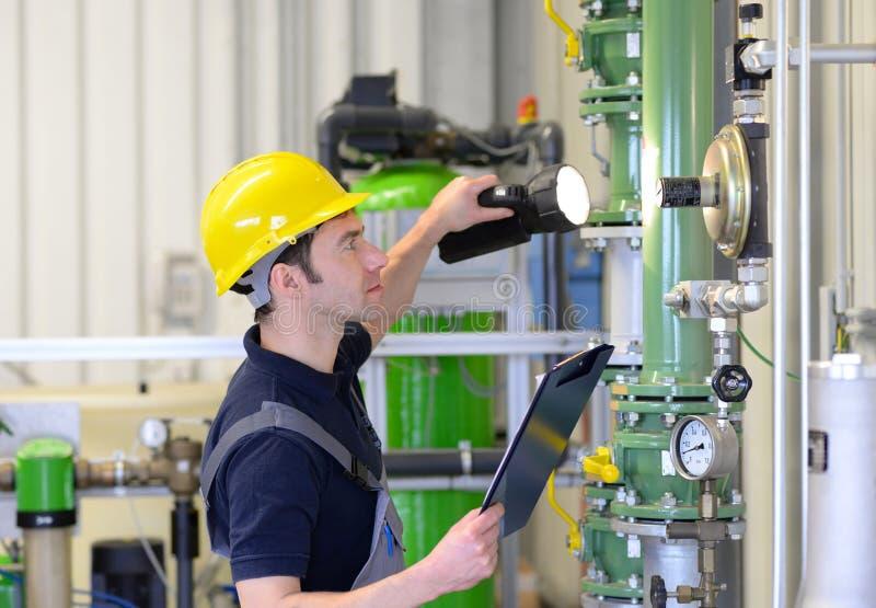 O trabalhador industrial inspeciona e repara um sistema de aquecimento em um fac imagens de stock