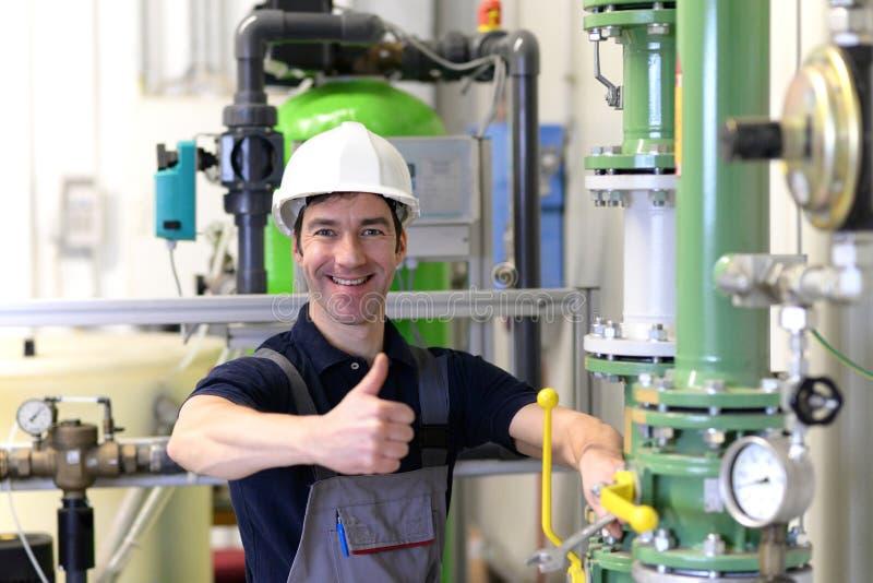 O trabalhador industrial repara máquinas e equipamento em uma refinaria imagem de stock royalty free
